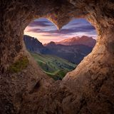 View from heart shape cave to the idyllic mountain scenery. Beautiful mountain landscape from hearth shaped entrance of rocky cave at sunrise. Valentines day royalty free stock photography