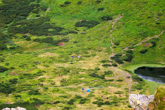 View from the height on the camping and group of tourists in Carpathian mountains. Stock Images