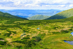 View from the height on the camping and group of tourists in Carpathian mountains, wild nature landscape. Royalty Free Stock Photography