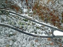 View from height on car driving through winter forest road. aeri. Al eye winter landscape Royalty Free Stock Photos