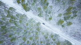 Aerial view on car driving through winter forest road. Scenic wi. View from height on car driving through winter forest road. Scenic winter landscape Royalty Free Stock Image