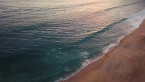 View from the height on a deserted beach. The Portuguese coast of the Atlantic Ocean. Aerial drone footage of ocean waves reaching shore stock footage