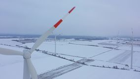 View from the height of energy producing wind turbines in winter, Poland. Aerial view of energy producing wind turbines in winter, Poland stock footage