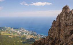 View from the height of the rocks to the sky,the sea and the village,located at the bottom, on the coast. Crimea royalty free stock images