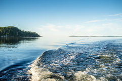 The view from the height of the water surface. Waves behind the boat with a motor in calm water, the view from the height of the water surface royalty free stock images