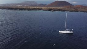 View from the height of the yacht near the lighthouse off the coast of Tenerife, Canary Islands, Spain. Aerial view of the yacht near the lighthouse off the stock footage