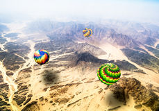 View from the heights of flying over mountains hot air balloons Royalty Free Stock Photo