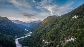 The view from the heights of the mountains and the river. The view from the heights of the mountains and river on background of blue cloudy sky Royalty Free Stock Photography