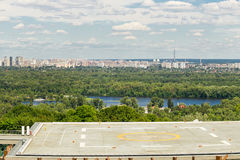 View of helipad on a rooftop of a building in a city park with panoramic metropolis view on the background Royalty Free Stock Photos