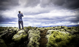The View From Here. A tourist snapping a photo of moss covered lava rocks in Vatnajokull National Park, Iceland Royalty Free Stock Images