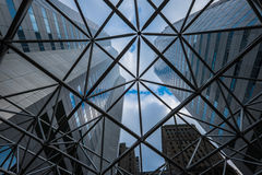 View of high-rise modern office buildings looking through steel mesh-like structure. View of high-rise modern office buildings and sky through a mesh-like steel Royalty Free Stock Photos
