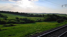 The view from the high-speed train on the beautiful scenery with hills and forest before sunset. The view from the. The view from the high-speed train on the stock video footage