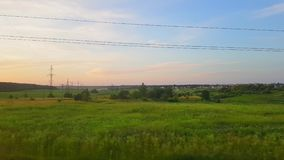The view from the train on the beautiful scenery with hills and forest before sunset. The view from the window of the. The view from the high-speed train on the stock footage