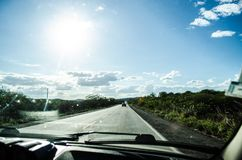View of a highway full of greenery on both sides inside a car and with the strong sun and blue sky. Refers to feelings of travel Stock Photography