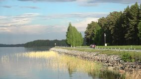 View of the highway near the lake Tuunaansalmi, summer evening. Finland. TUUNAANSALMI, FINLAND - 16 JUNE, 2017: View of the highway near the lake Tuunaansalmi stock video footage