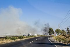 View of a highway observing a fire with black smoke and cars circulating royalty free stock image