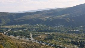 View of the highway road at the mountain area near river. In 4K stock footage