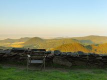 View from hill over rest place with old wooden chair down to countryside. Spring morning. On the peak of hill Royalty Free Stock Image