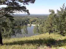 View from the hill to a small Siberian lake, Krasnoyarsk region. Siberian landscape with pines and birches. View from a high hill to the lake. Summer, green stock photo
