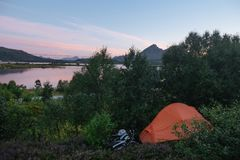 View from hill to the tent and lake and mountains in the Norway at summer time on sunset royalty free stock image