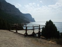 View from hill with wooden bridge handrails and pine tree on coastline Black sea. Crimea. View from hill with wooden handrails and pine trees on coastline Black royalty free stock image
