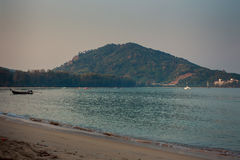 View of hilly island yacht boat in azure sea beach on foreground. Panorama of green hilly island with yacht and boat in azure sea and sand beach on foreground Stock Photography