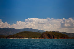 View of hilly islands azure sea against blue sky cumulus clouds Stock Images