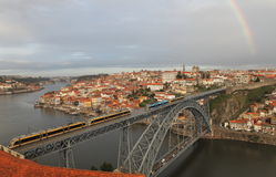 View of the historic city of Porto with the Dom Luis bridge, metro train and rainbow Royalty Free Stock Photo