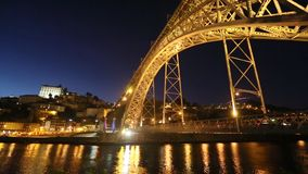 View of the historic city of Porto, Portugal with the Dom Luiz I bridge at night time. stock footage