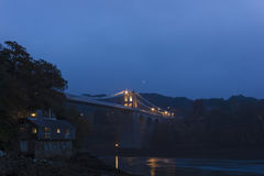 View of the historic Menai Suspension Bridge illuminated at night-time, Isle of Anglesy, North Wales. Grand night-time view of the historic Menai Suspension Stock Images