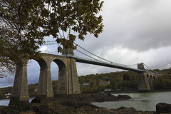 View of historic Menai Suspension Bridge from the Menai Straits, Isle of Anglesey, Wales Royalty Free Stock Images