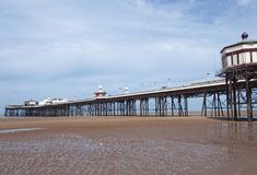 View of the historic victorian north pier in blackpool with the kiosks and buildings with the beach visible at low tide on a brigh. A view of the historic stock images