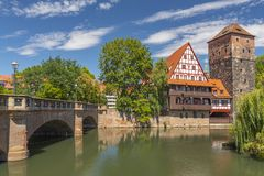 Historic Wine Vault or Weinstadel, water tower and Hangmans Way or Henkersteg beside Pegnitz River in Nuremberg, Germany. stock photos