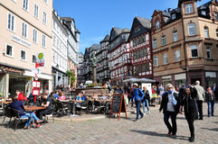 View of historical buildings, outdoor cafe seating, Marburg. View of historical buildings, full of people in outdoor cafe seating, statue of St. George in Royalty Free Stock Images