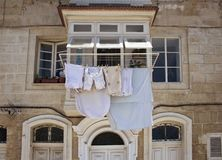 View of a historical, typical Valletta building. In Malta. Hanging out clothes outside to dry reflects region`s culture and lifestyle Stock Image