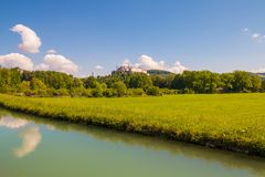 View of Hohensalzburg Castle Festung Hohensalzburg over meadow. Beautiful view of Hohensalzburg Castle Festung Hohensalzburg over green alpine meadow and water Royalty Free Stock Image