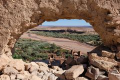 View through a hole in Ancient Kasbah in Ait-Ben-Haddou, Morocoo. Ait Benhaddou, famous ancient berber kasbah, Morocco.Panorama of Ait Benhaddou Casbah near Stock Image