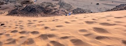 View from the holy mountain Jebal Barkal in Karima, Sudan perpendicular to the sand dune on the western slope with locals climbing. The dune stock images