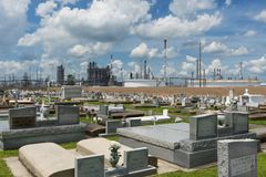View of the Holy Rosary Cemetery in Taft, Louisiana, with a petrochemical plant on the background. Stock Photography
