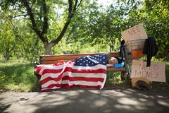 View of a homeless man lying on bench covered with USA flag. Stock Images