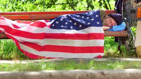 View of a homeless man lying on bench covered with USA flag. Poor man living in street, using USA flag as blanket stock video footage