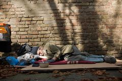 View of homeless man sleeping on cardboard on the ground. stock image