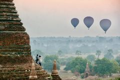 View of hot air balloons over plains in Myanmar. At sunrise, the hot air balloons cross over the horizon in Myanmar. People watch and take photos while the sun Stock Images