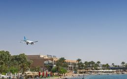 Sunny day in Eilat - famous resort city in Israel. View on hotel zone, shopping center, sand beaches and landing airplane Stock Photo