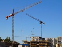 Three cranes at work. View of the house construction site. royalty free stock photography