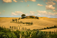 View of house with cypress trees in a field in the tuscan region Stock Photos