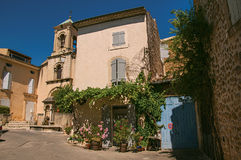View of house with flowers and church with steeple, in front of a square of Lourmarin. View of house with flowers and church with steeple, in front of a square Stock Image