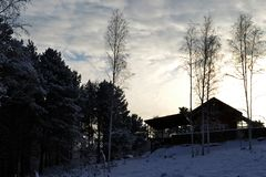 View of the house on a hill among the snowy forest in the rays of the setting sun in winter stock photos