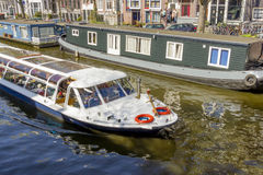 View on houseboats, Amsterdam, the Netherlands. View on the houseboats with cruiseboat in Amsterdam the Netherlands Stock Photos