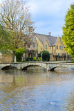 View of houses along walking bridge over the water in Bourton On Stock Photography